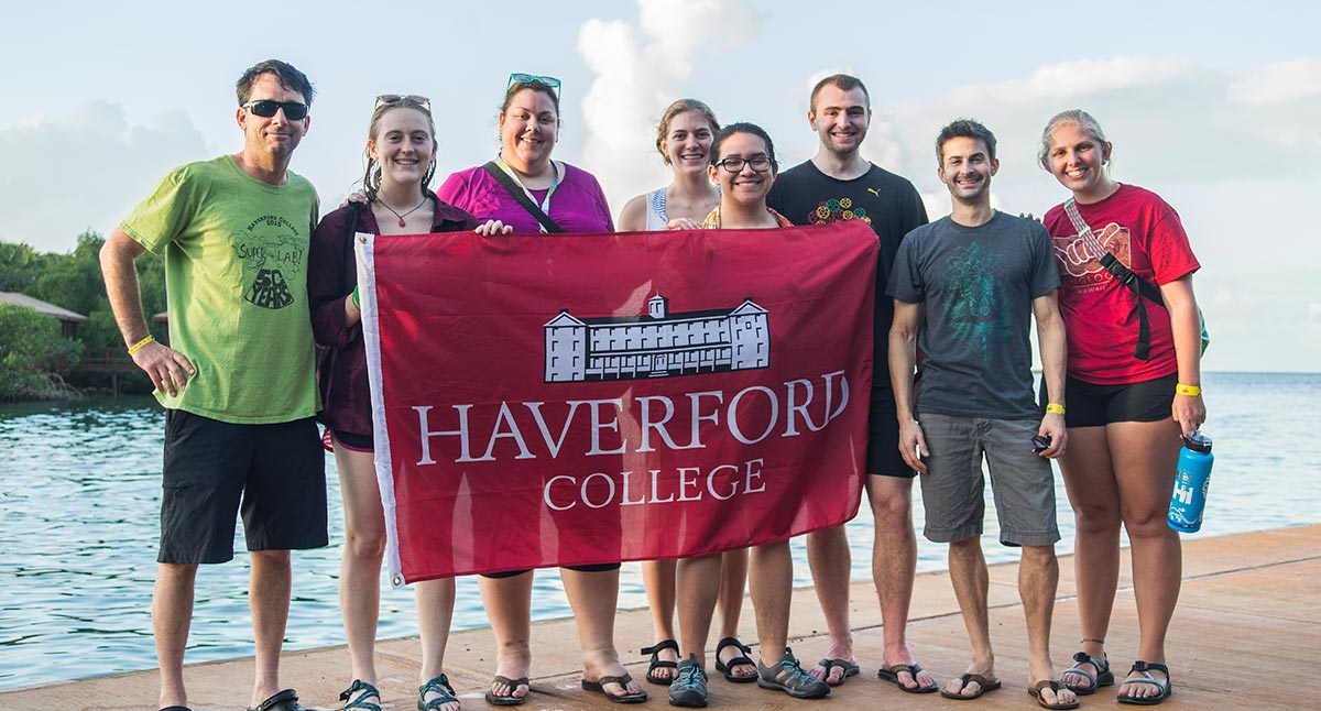Haverford faculty and students pose in the field with a Haverford College banner