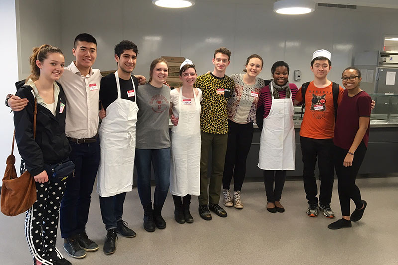A group of participants posing together in a kitchen