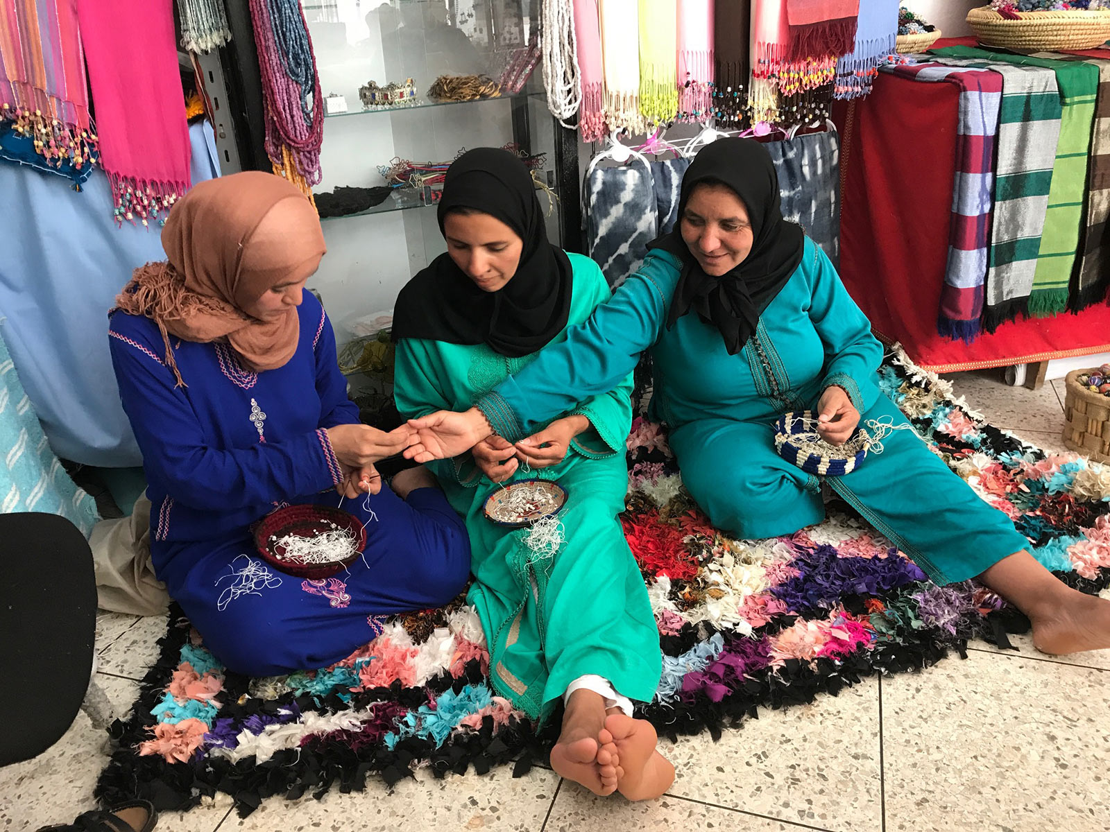 Women sitting together on the floor making jewelry