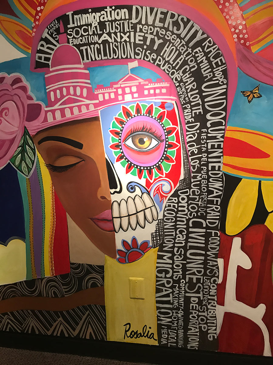 Wall mural showing half a woman's face in sugar-skull style