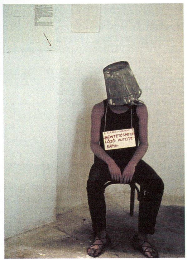 A man sits on a stool with a bucket on his head