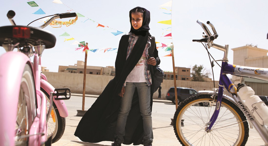 A young Saudi girl stares longingly at bicycles