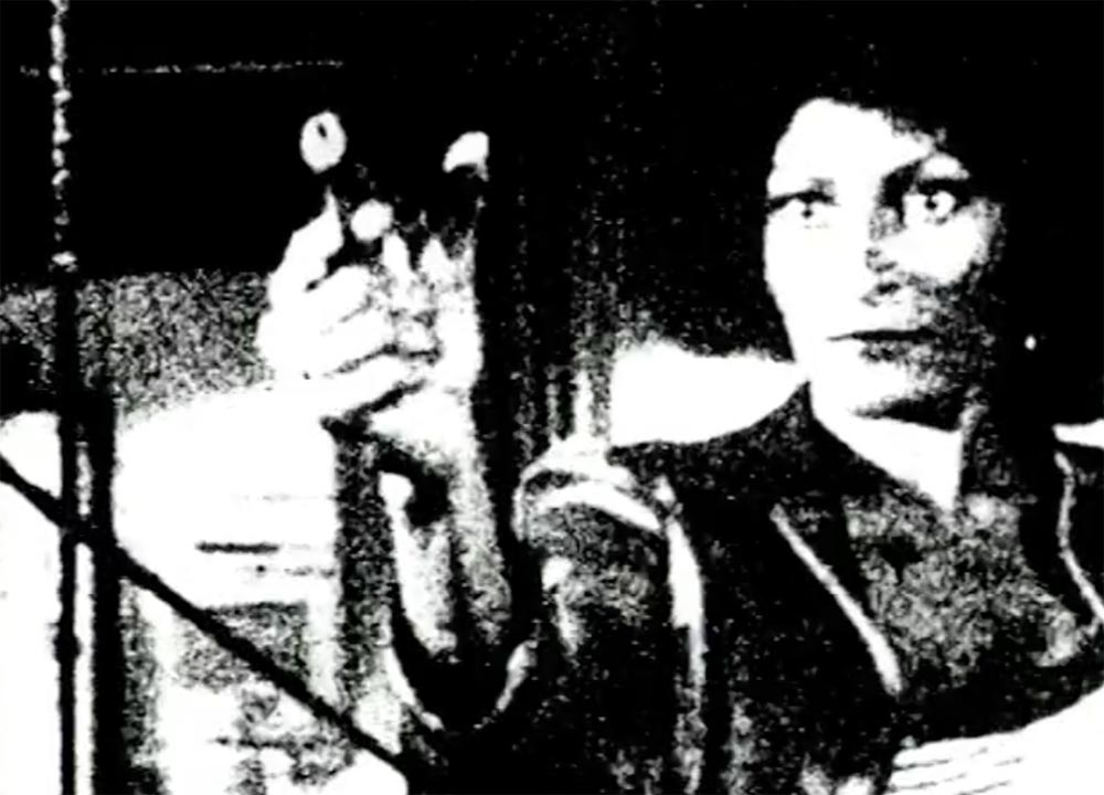 Grainy film still of a woman holding a gun