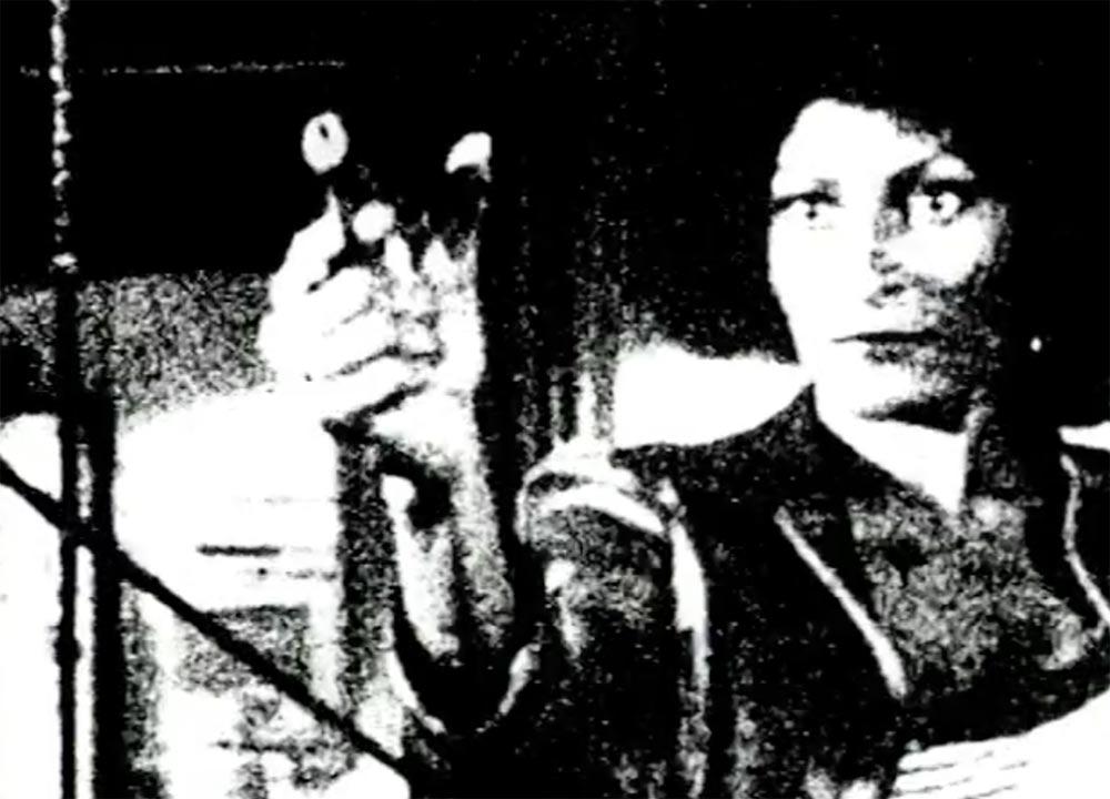 Grainy film still of a woman holding a gun