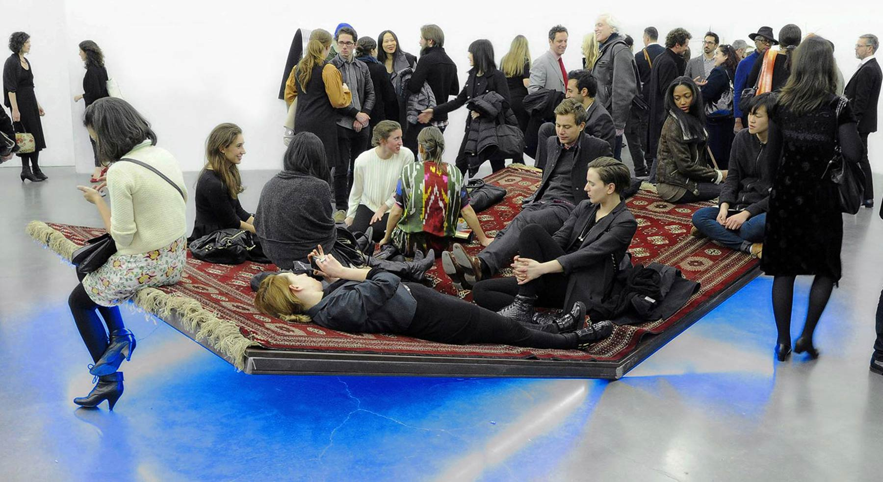 People sit on an angled carpet at an exhibition in New York