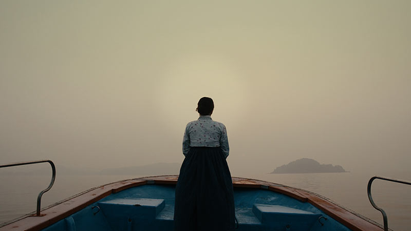 Woman standing at prow of boat sliding along misty waters
