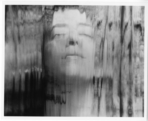 Distorted black and white photo of a woman's face