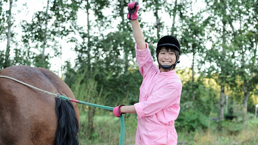 A city-kid dressed in pink riding gear holds a fist up in triumph while standing behind a horse