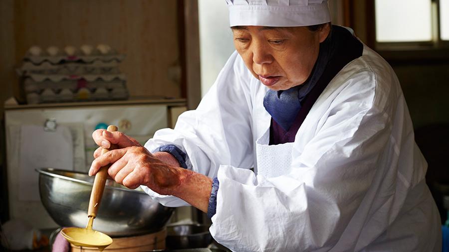 A chef carefully ladles batter onto a skillet