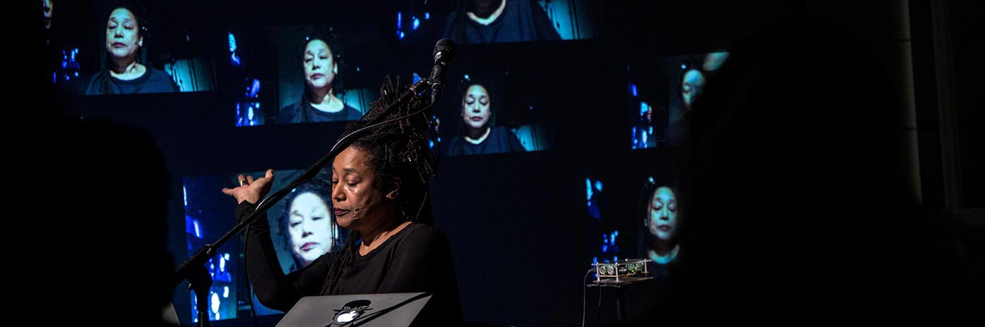 Pamela Z surrounded by screens with her face on them during a performance