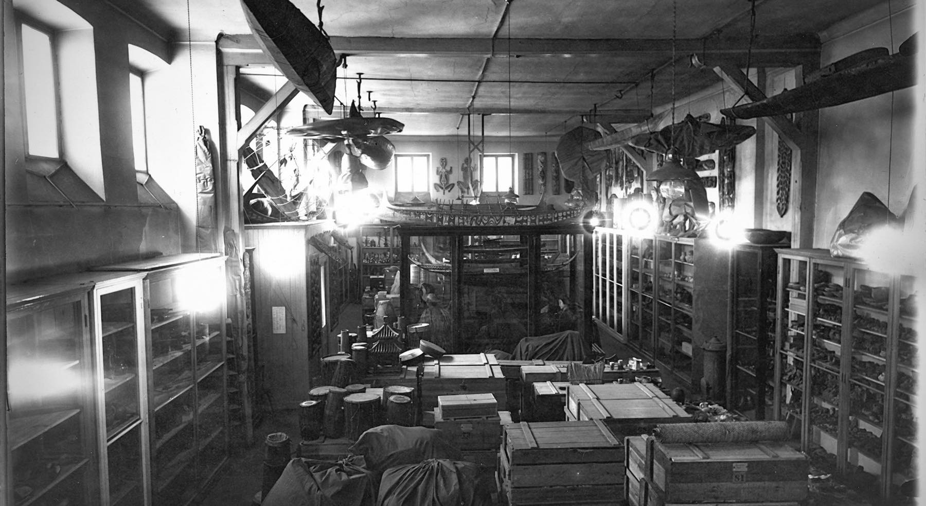 Black and white photo of a room jam packed with artifacts