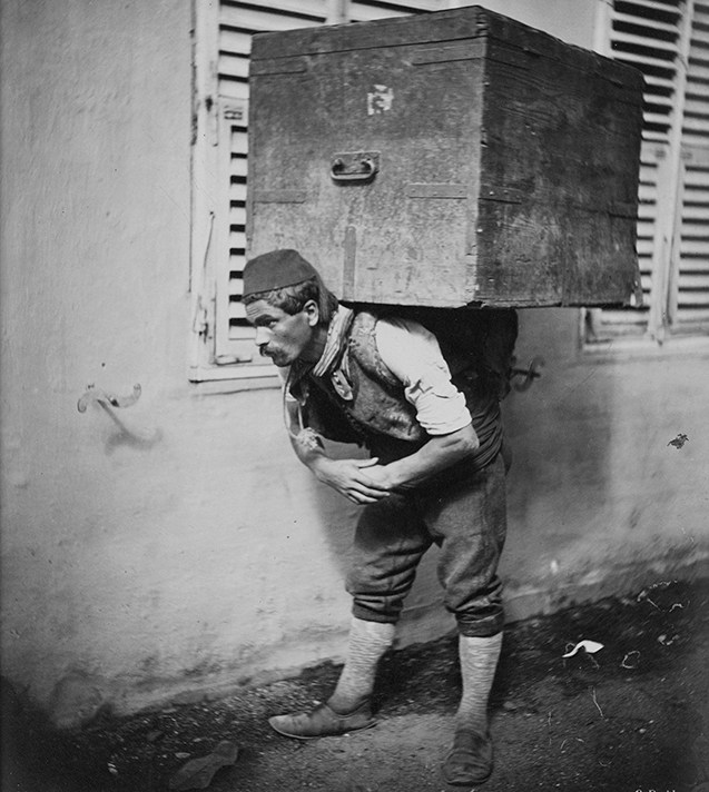 A man is bent double carrying a trunk on his back