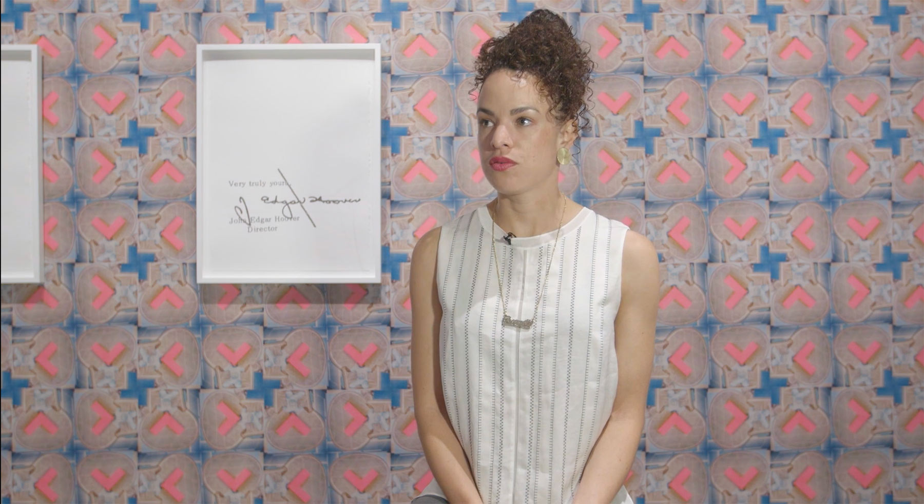 Sadie Barnette standing in the Cantor Fitzgerald Gallery with her artwork in the background