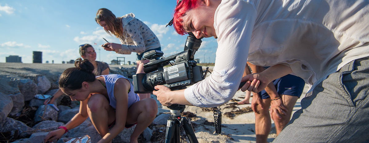 Students filming a documentary on the beach