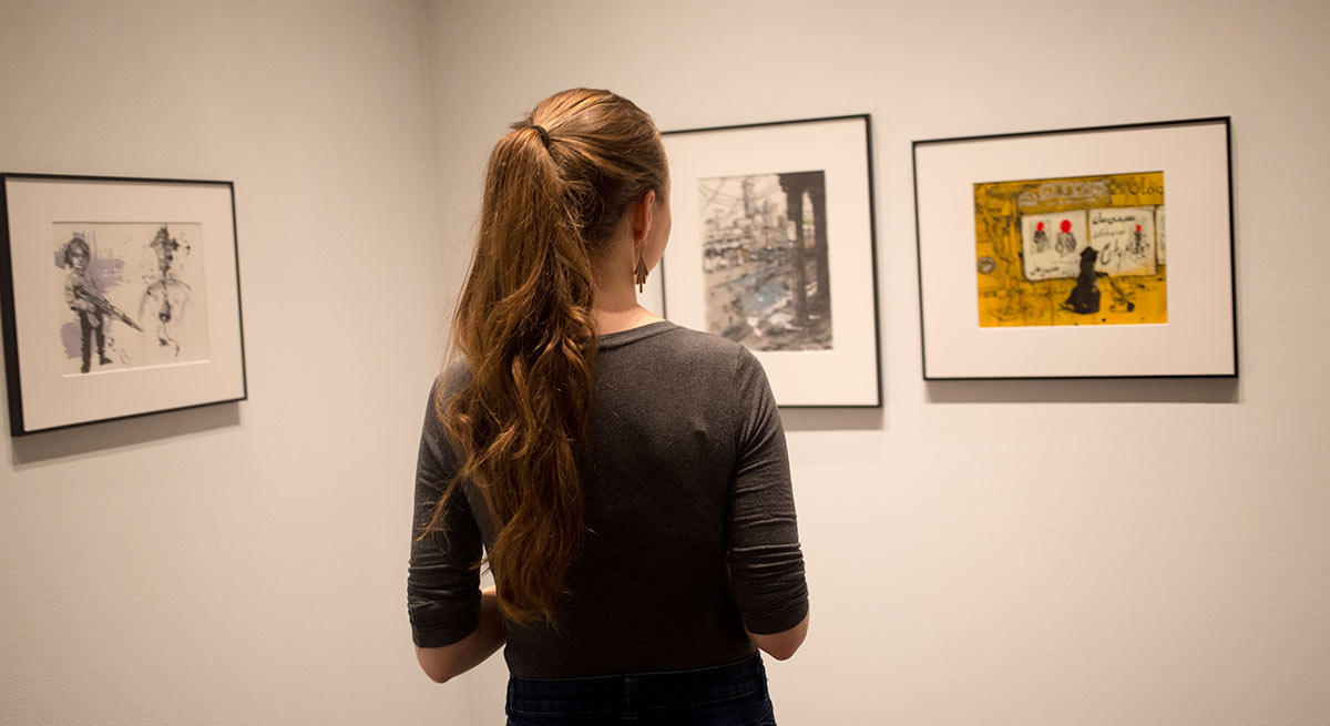 A student studies illustrations hung in the Cantor Fitzgerald Gallery