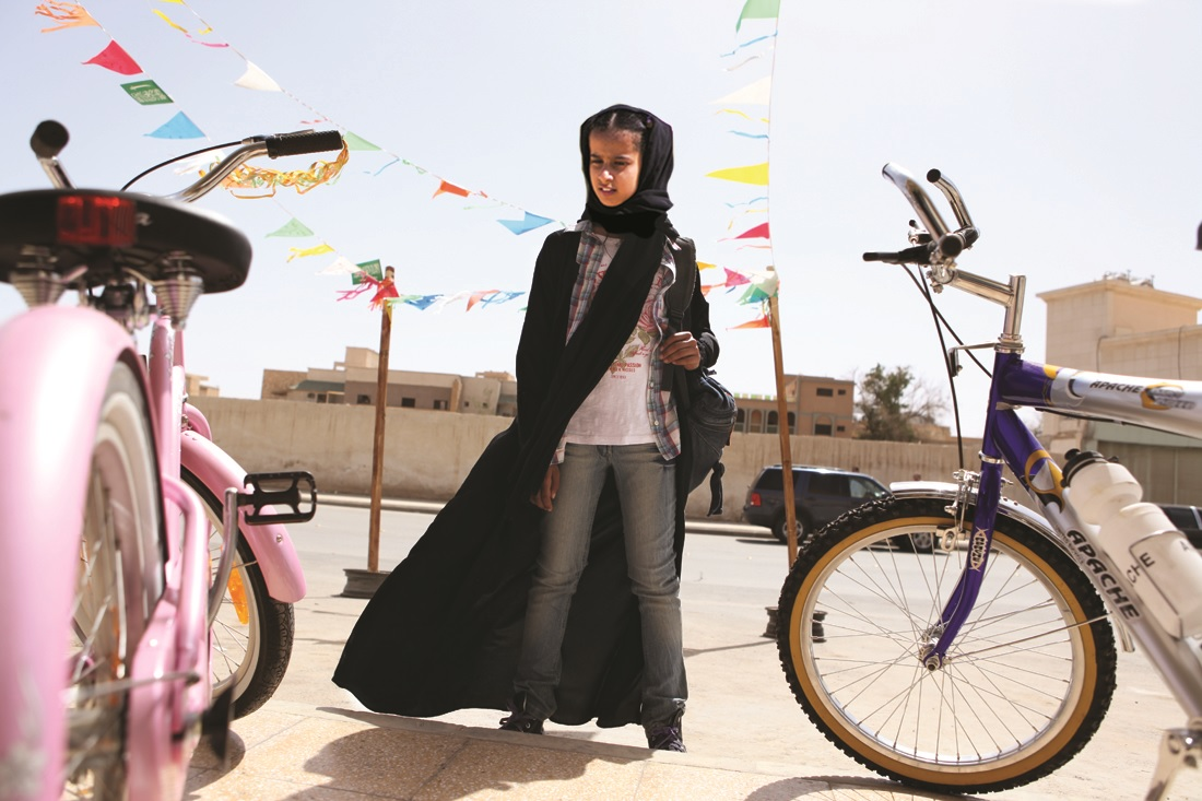 A young Saudi girl stares longingly at bicycles