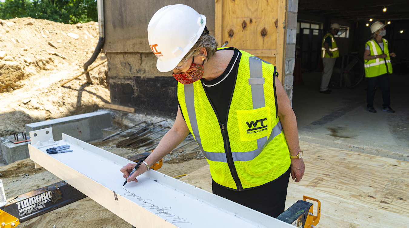 President Wendy Raymond signs the beam which will be used in the construction of the Michael Jaharis Concert Hall.