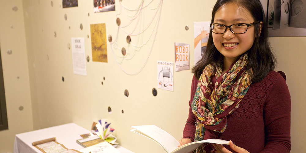 Honglan Huang holds a book in front of her exhibition