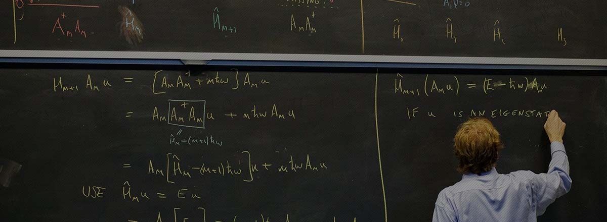 Peter Love at chalkboard covered with physics equations.