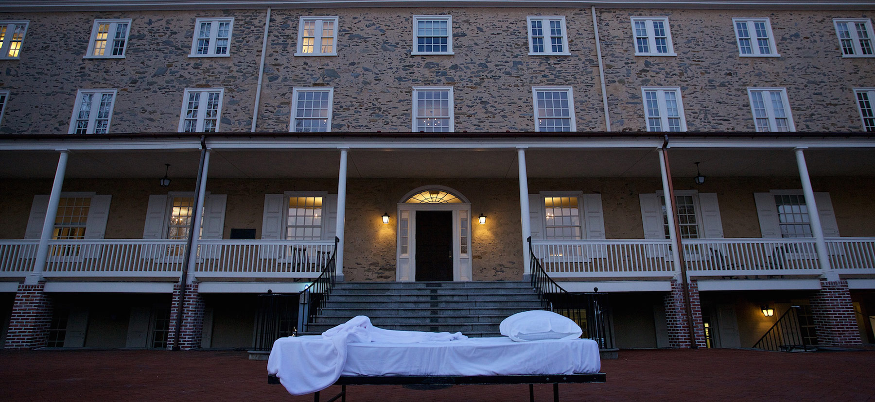 A student's bed in front of Founders Hall