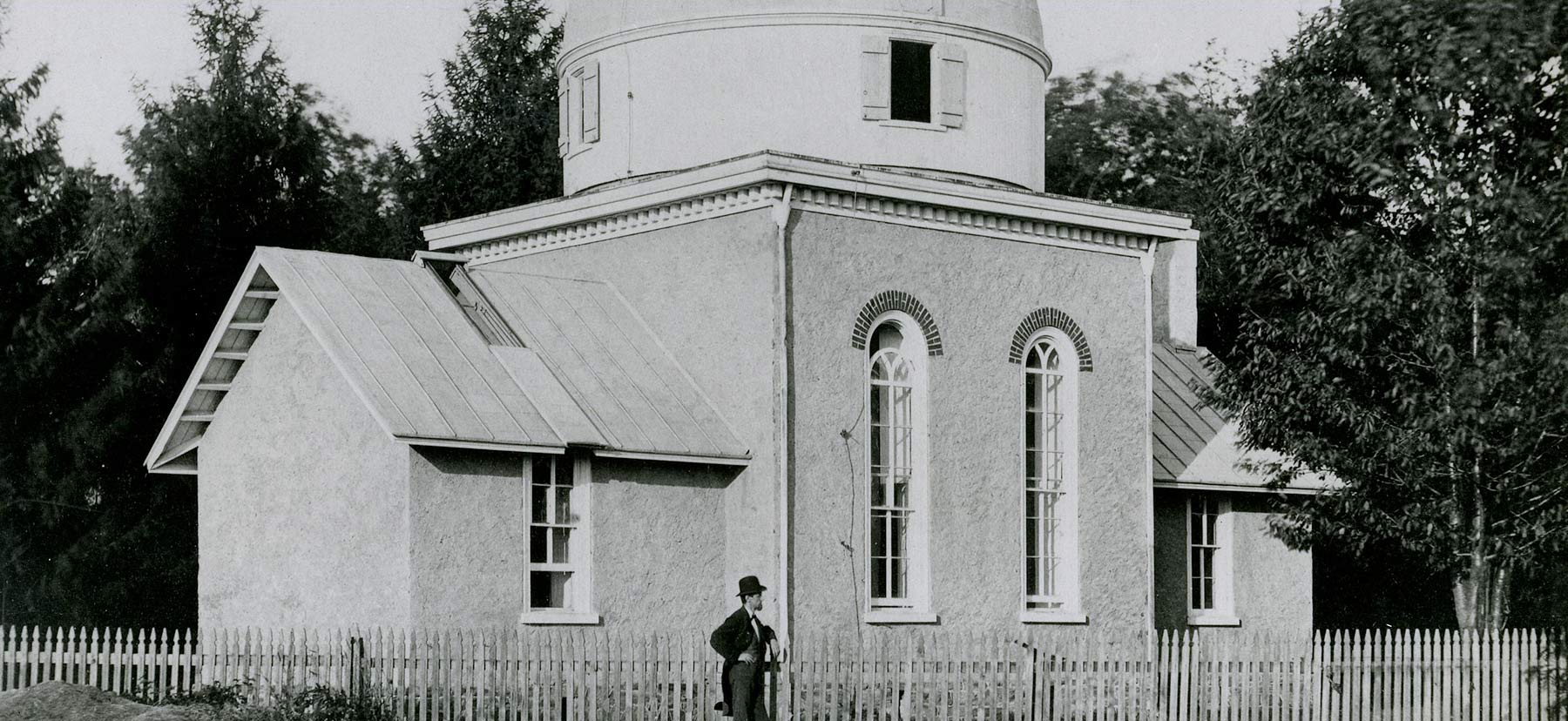 A photo of a man standing in front of an observatory