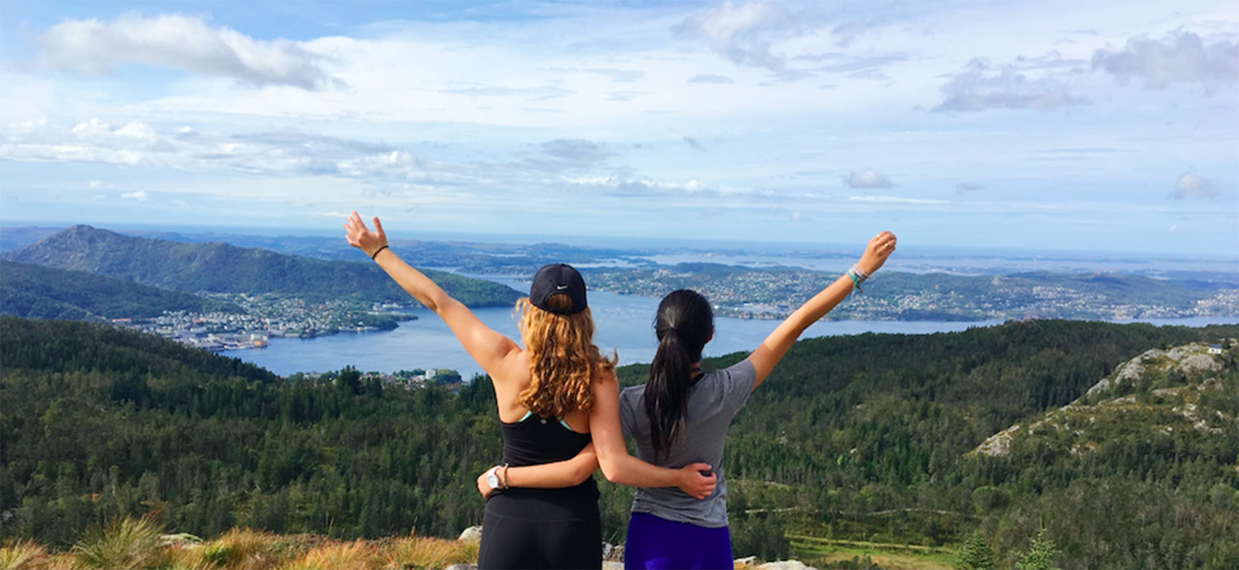 Two women stand with their arms raised, backs to the camera, with Fjords spread out in front of them