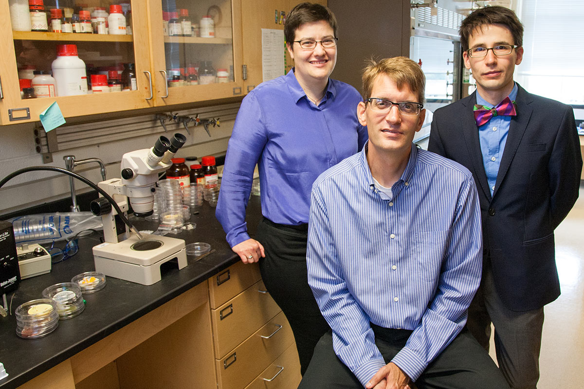 Three faculty members posing in a lab