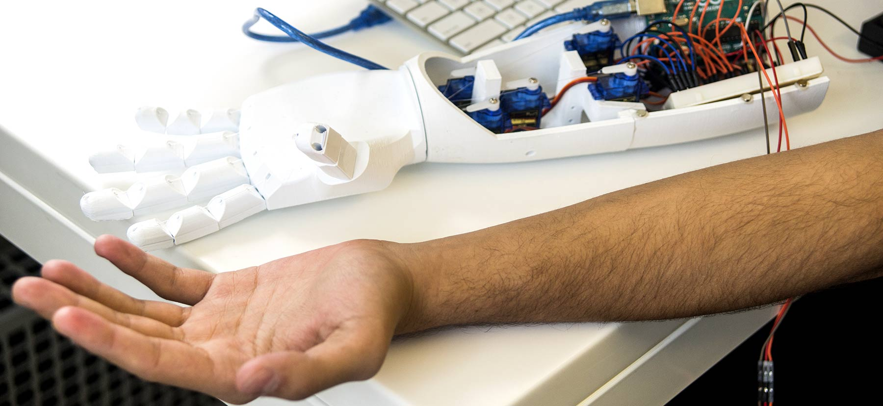 Mohamed's arm stretched out beside the mechanical arm he created, which is opened to expose various wires