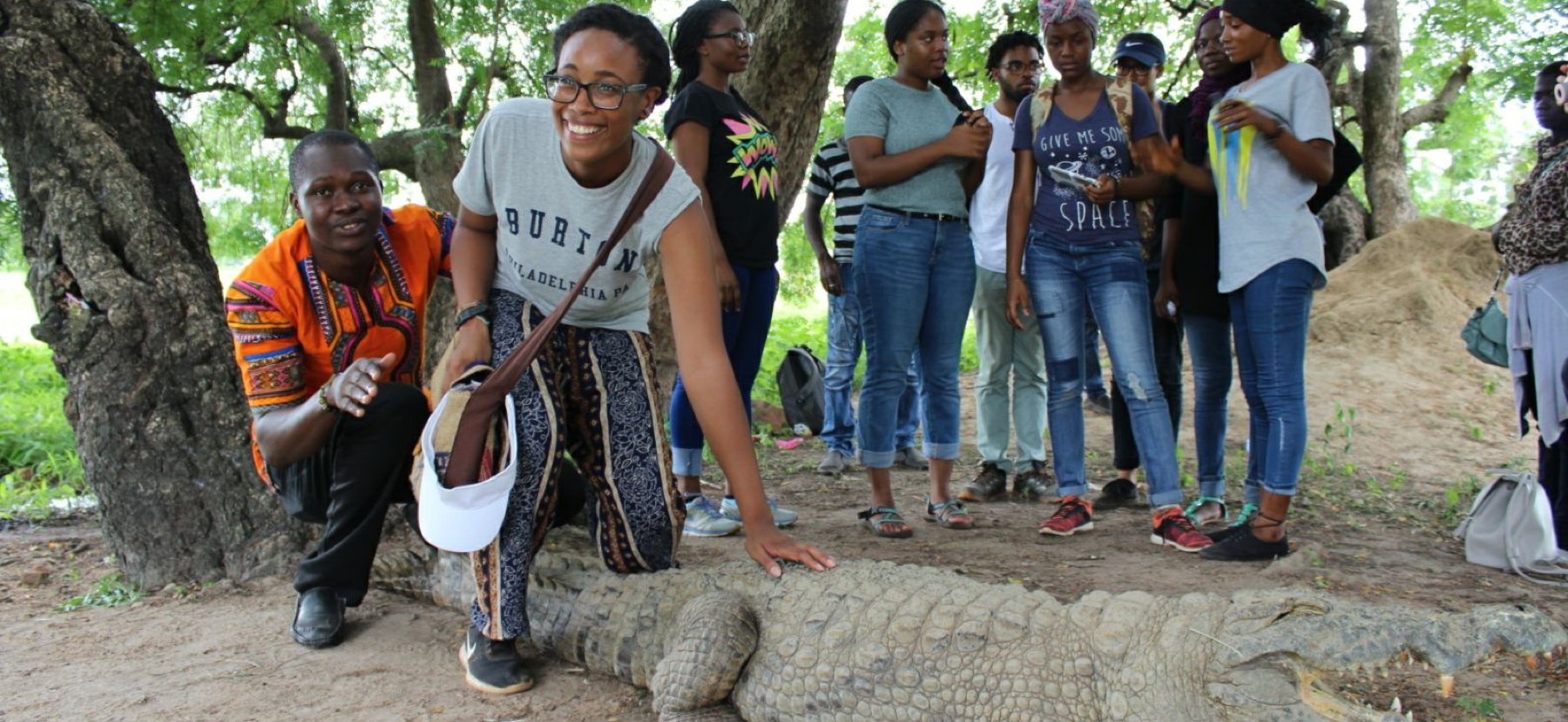 Woman leans over to pet an alligator in front of a group of people.