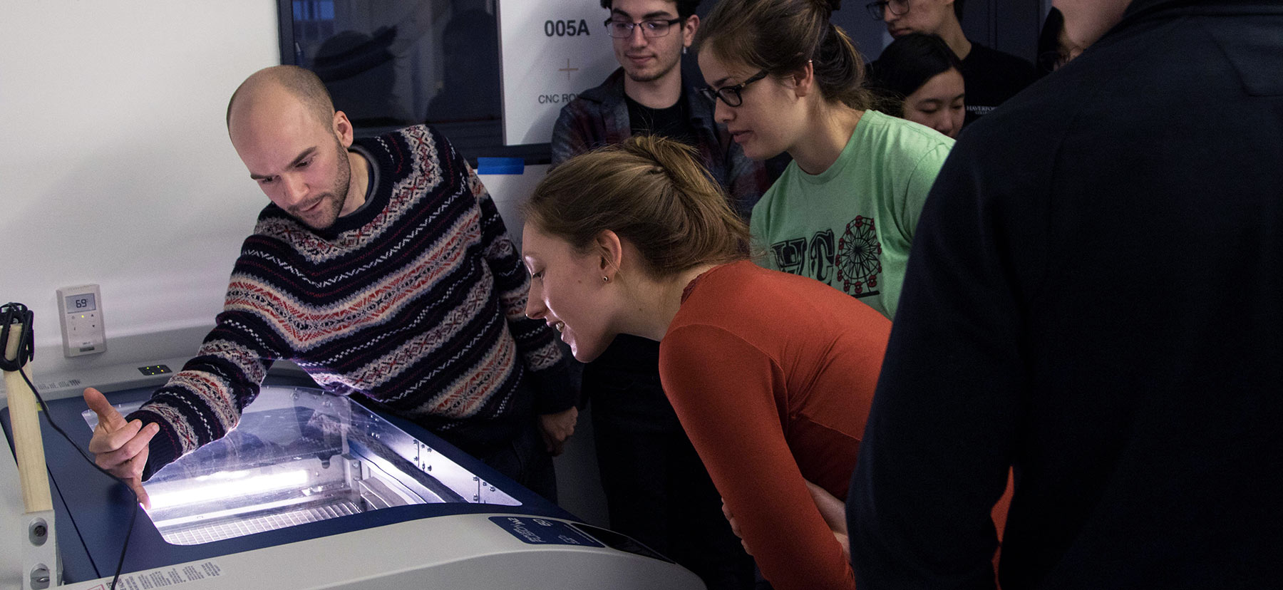 A group examines a large laser cutter