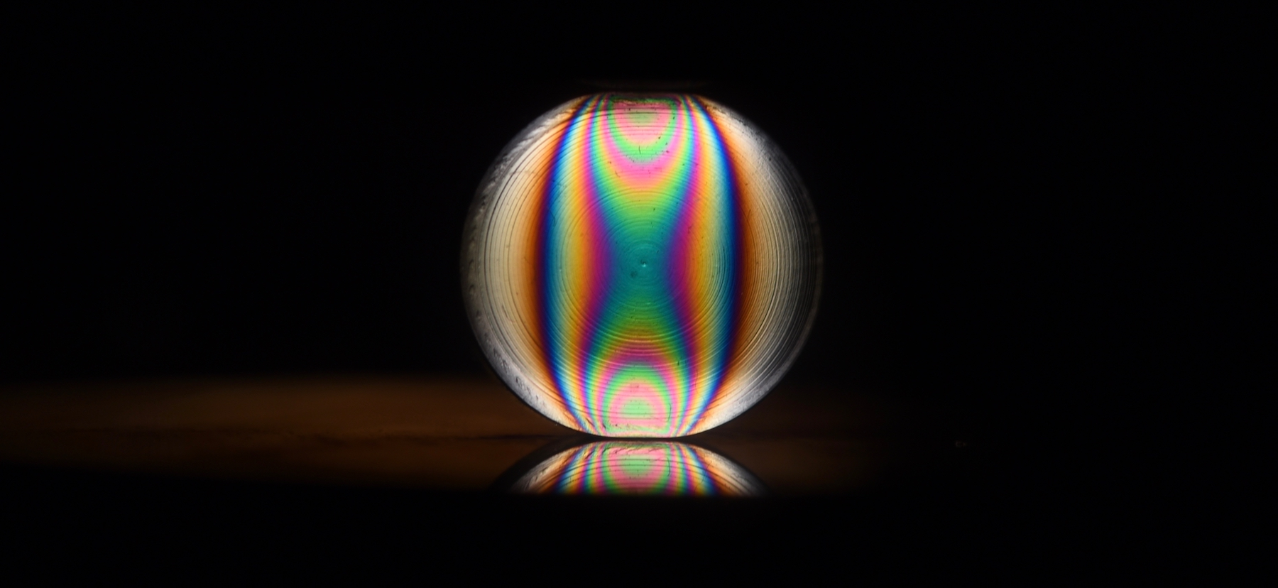 Fringes in a photoelastic particle when it was squeezed diametrically.