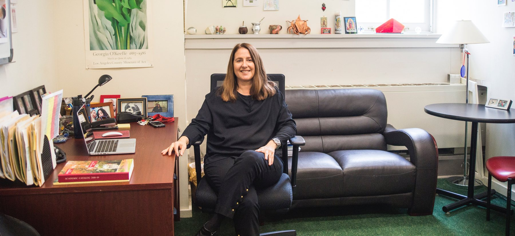 A woman sits at a desk