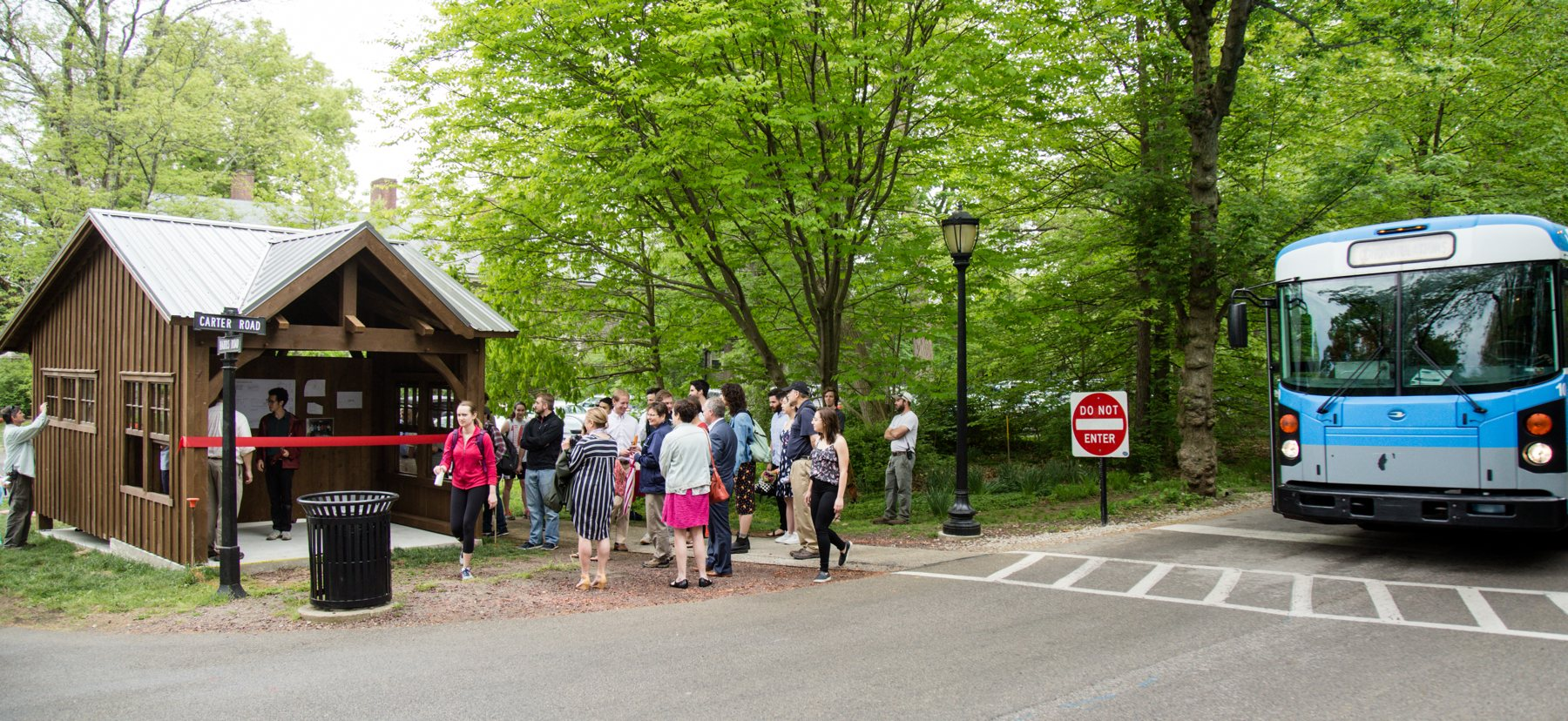 A bus stop on campus with a crowd of people and a bus