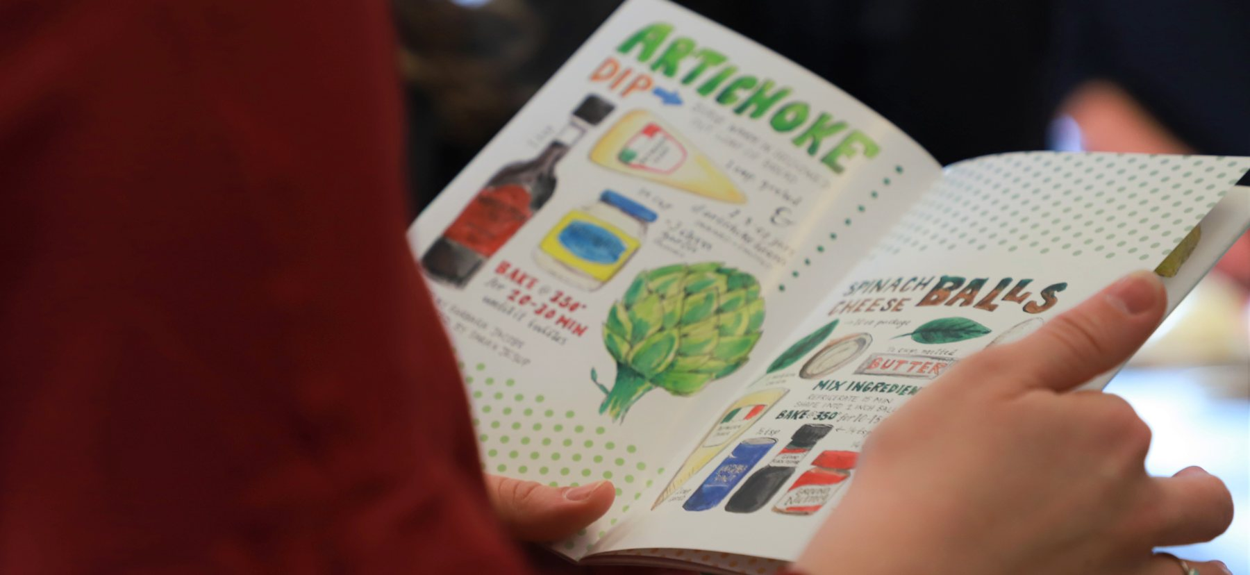 A person views an illustrated recipe for artichoke dip