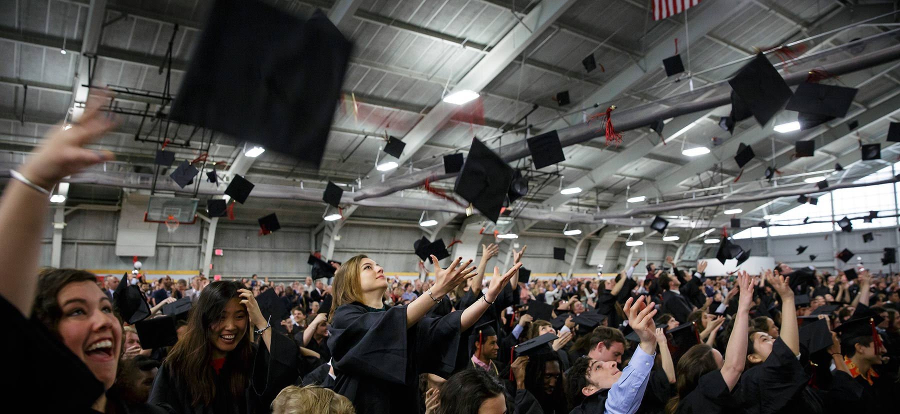 Graduates throw caps in the air