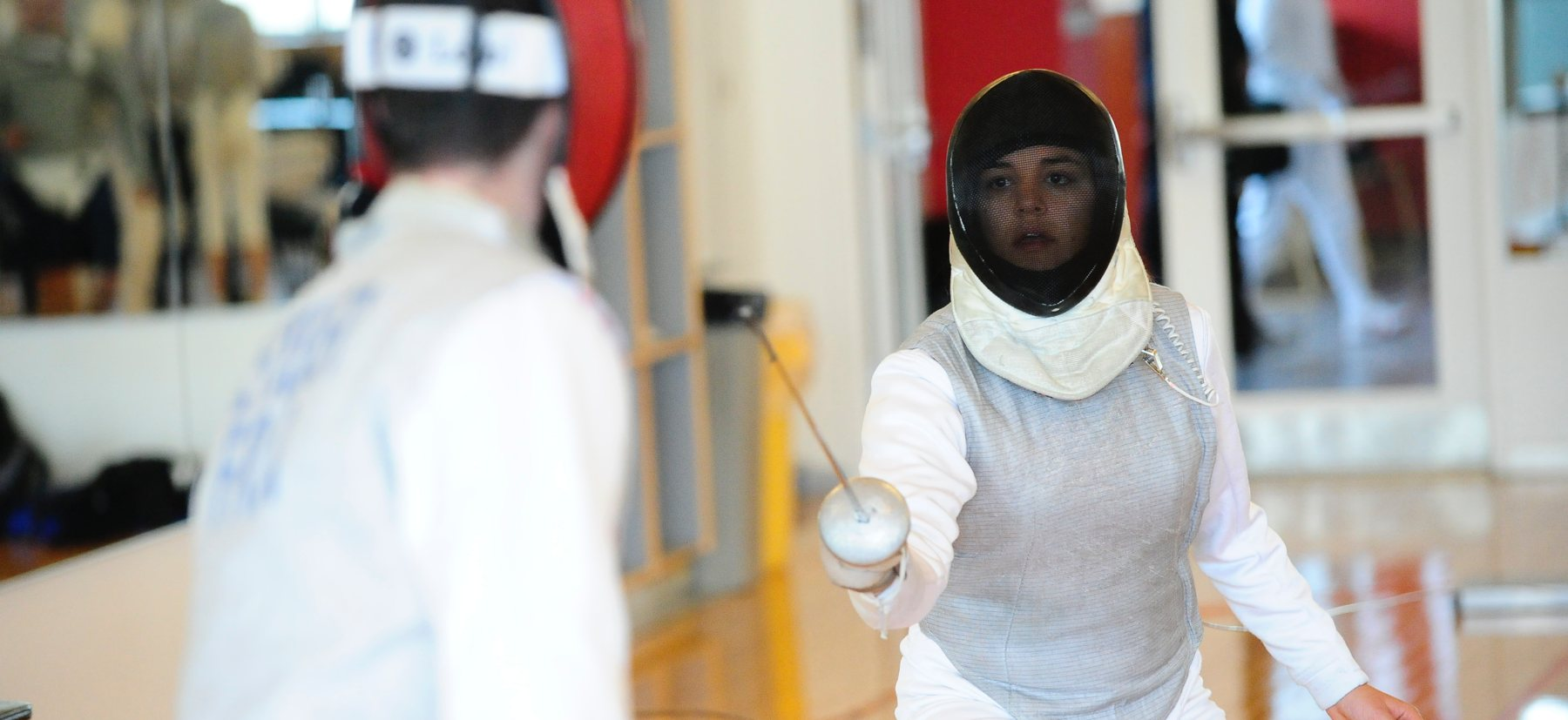 Woman competing in fencing match