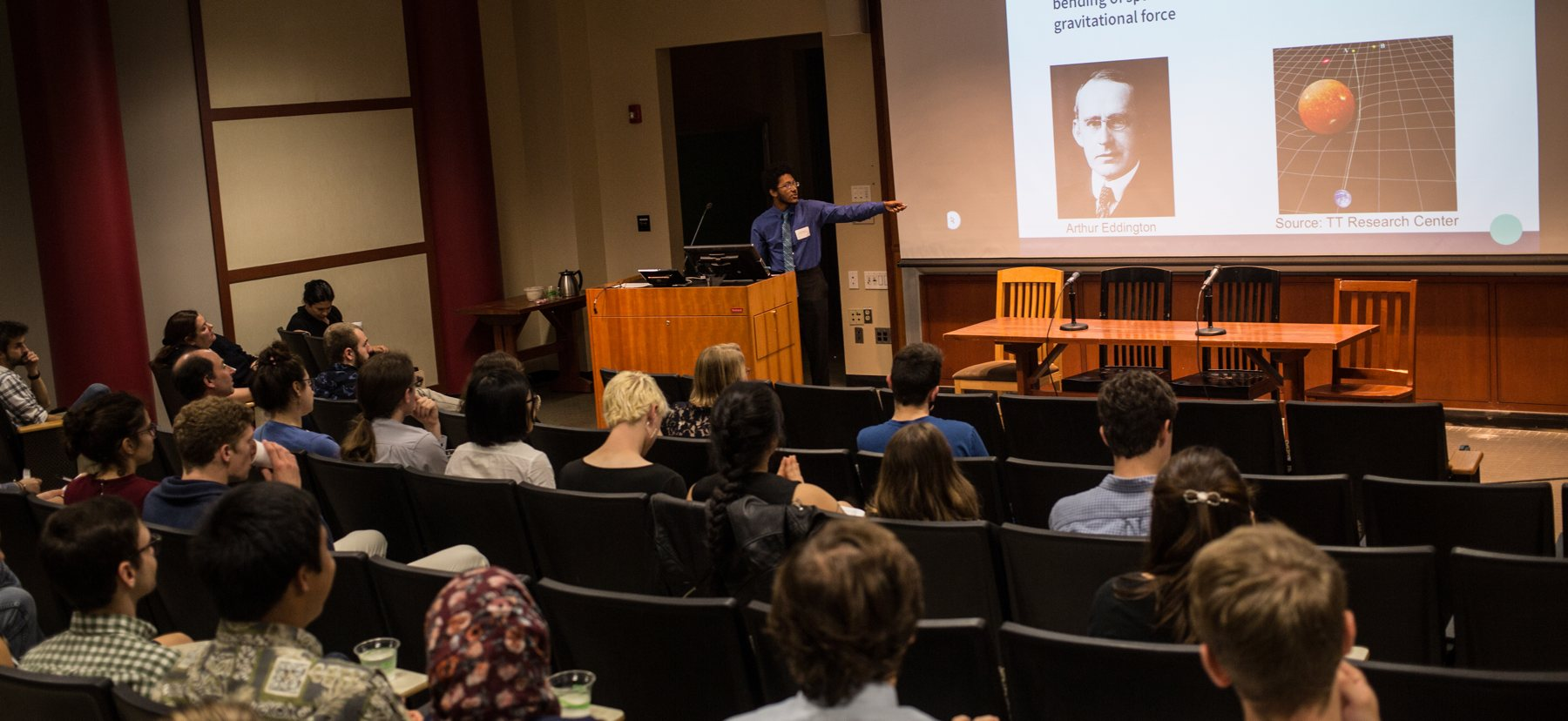 A person presents on research in front of an audience.