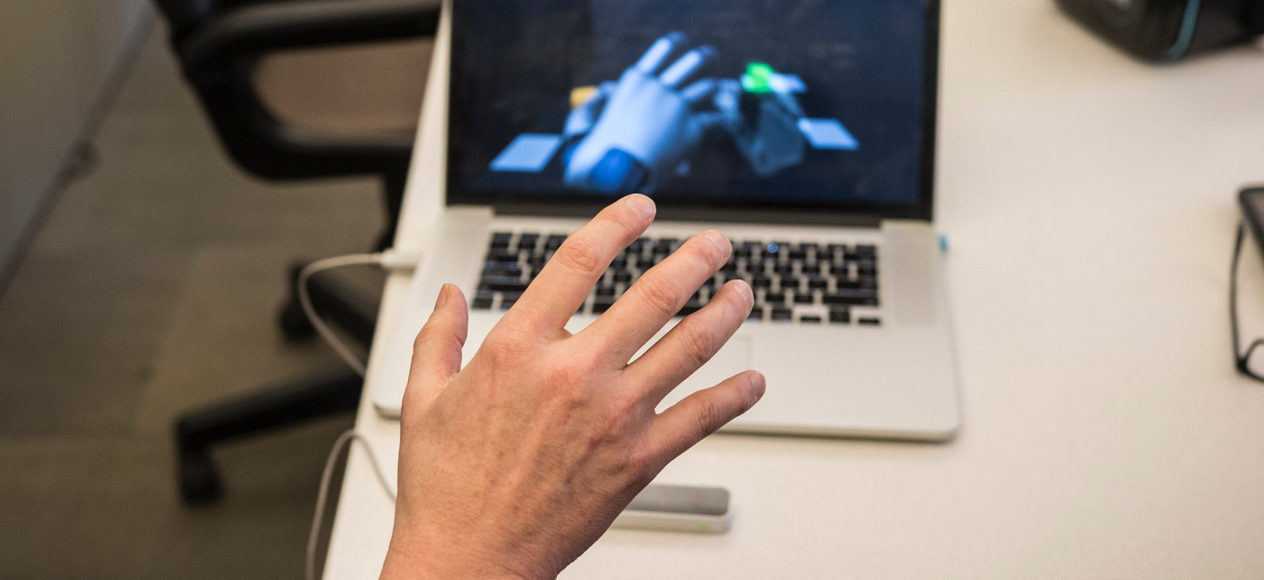 A person reaches out in front of a laptop using peripheral to interface with a computer.