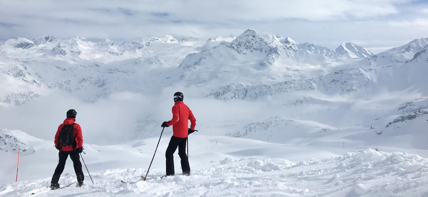 two skiers look out at large mountain covered in snow