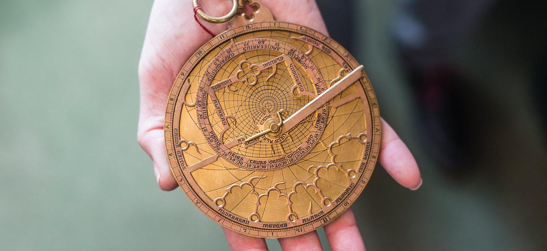 A hand holding an astrolabe.