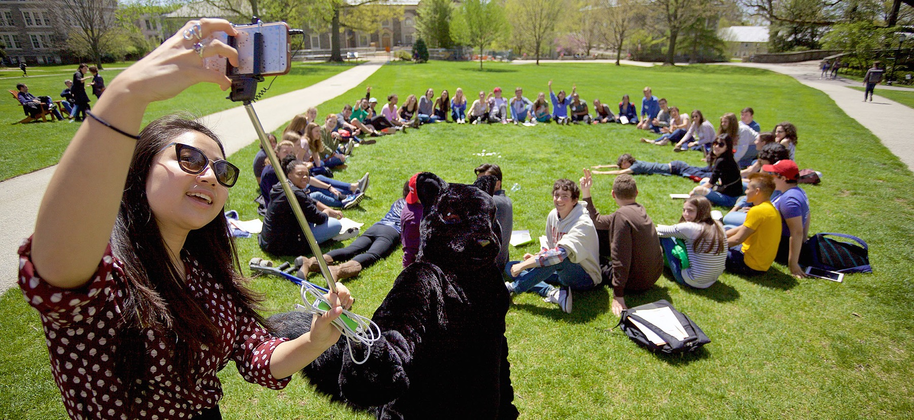 Black squirrel mascot taking a selfie with students sitting in a circle on grass.