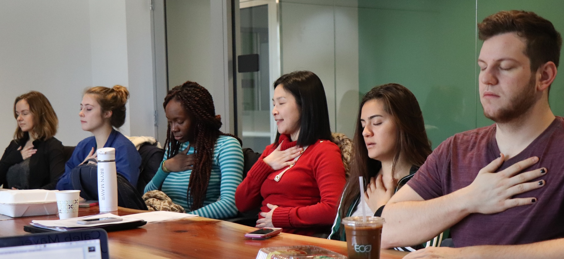 Students and a professor sit with hands over their hearts in a mindfulness exercise