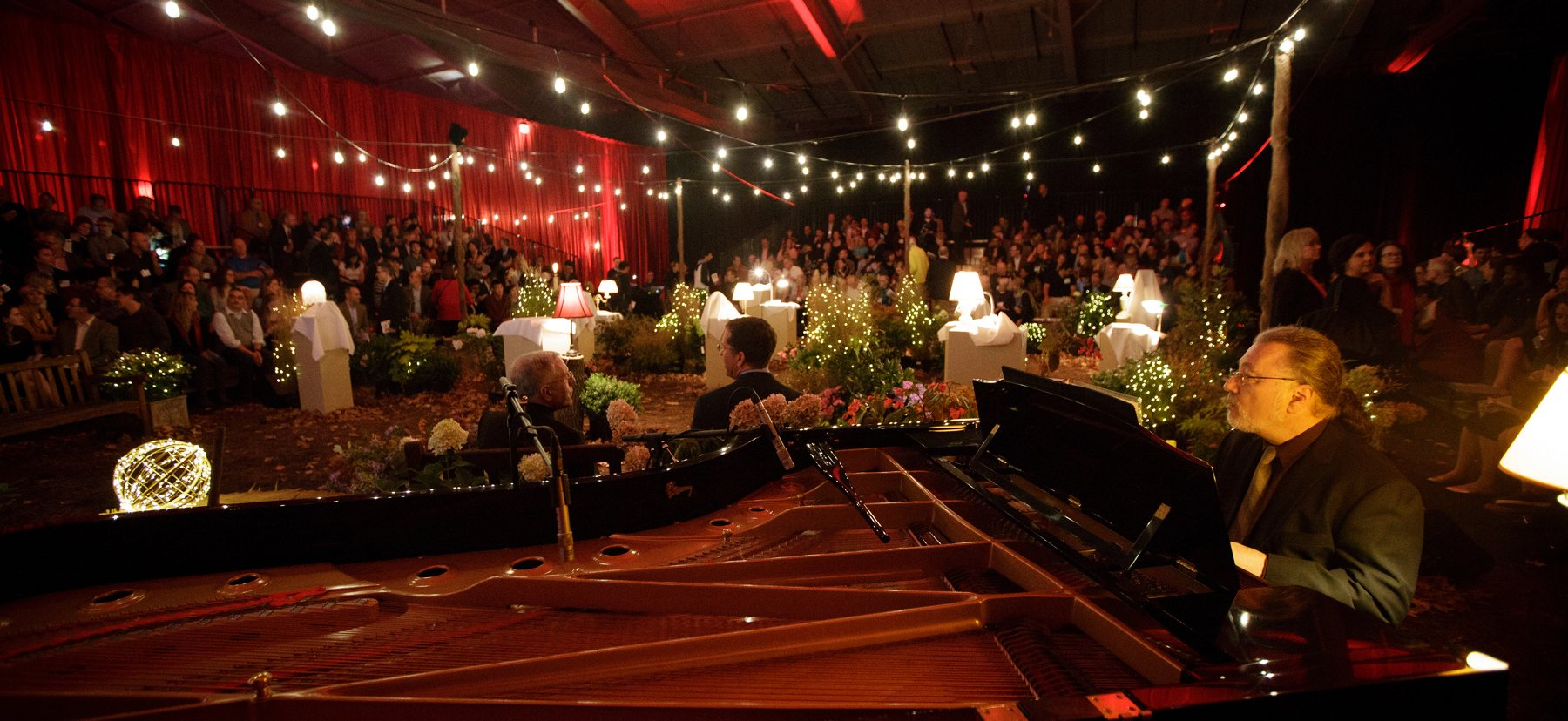 A man in the foreground plays piano in front of a celebration gala