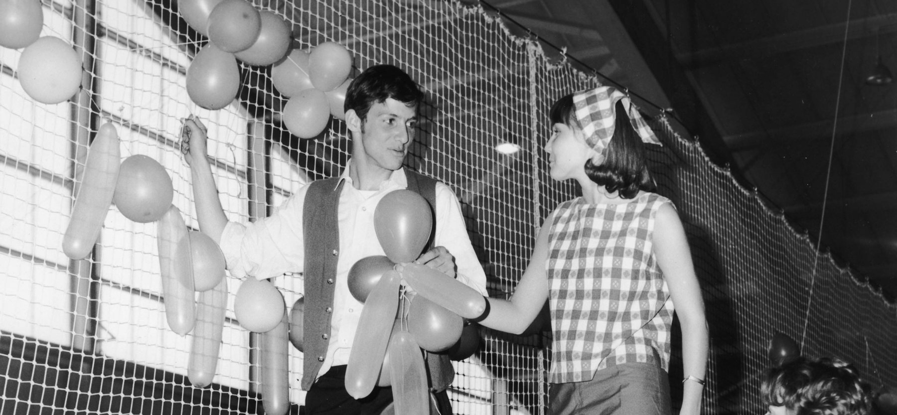 A man and a woman hang balloons in the Field House circa 1965