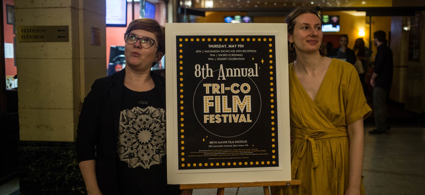 two women stand on either side of a sign promoting a film festival