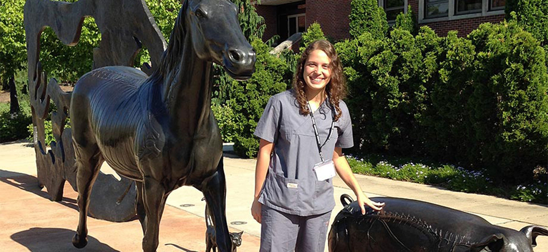 Natalia Amaral Marrero posing with statues of a horse and pig