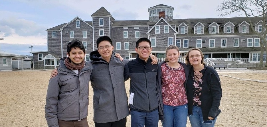 Junior Nguyen and friends on a beach with a house in the background
