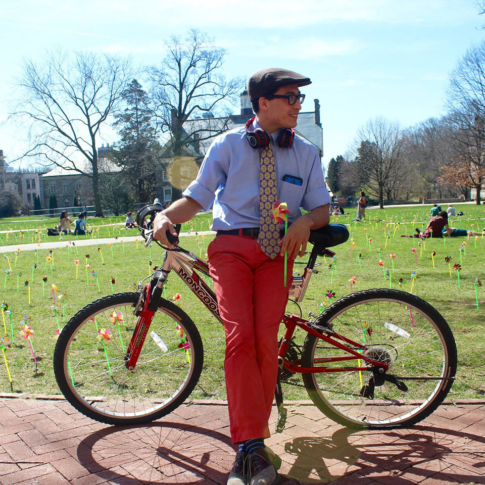 Antonio Gill standing with his bike, a pinwheel covered Founders Green behind him