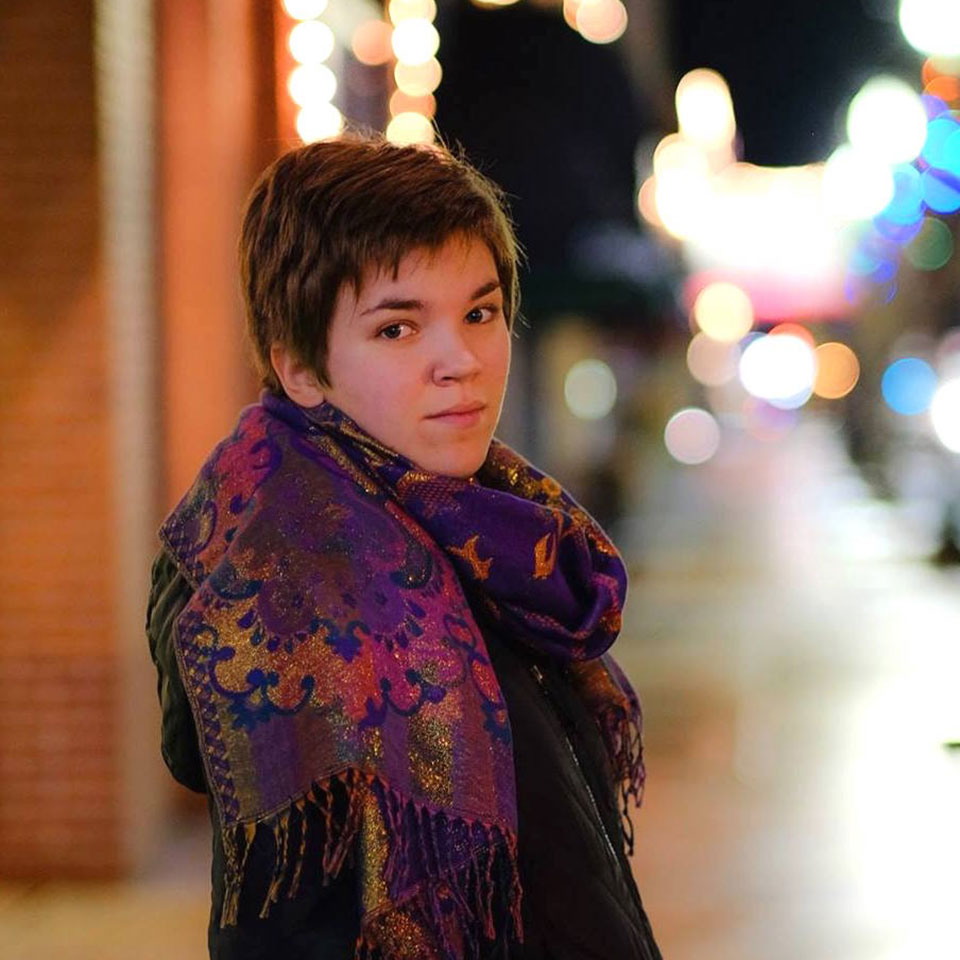 Stephanie Widzowski wearing a vibrant scarf, photographed on a street at night