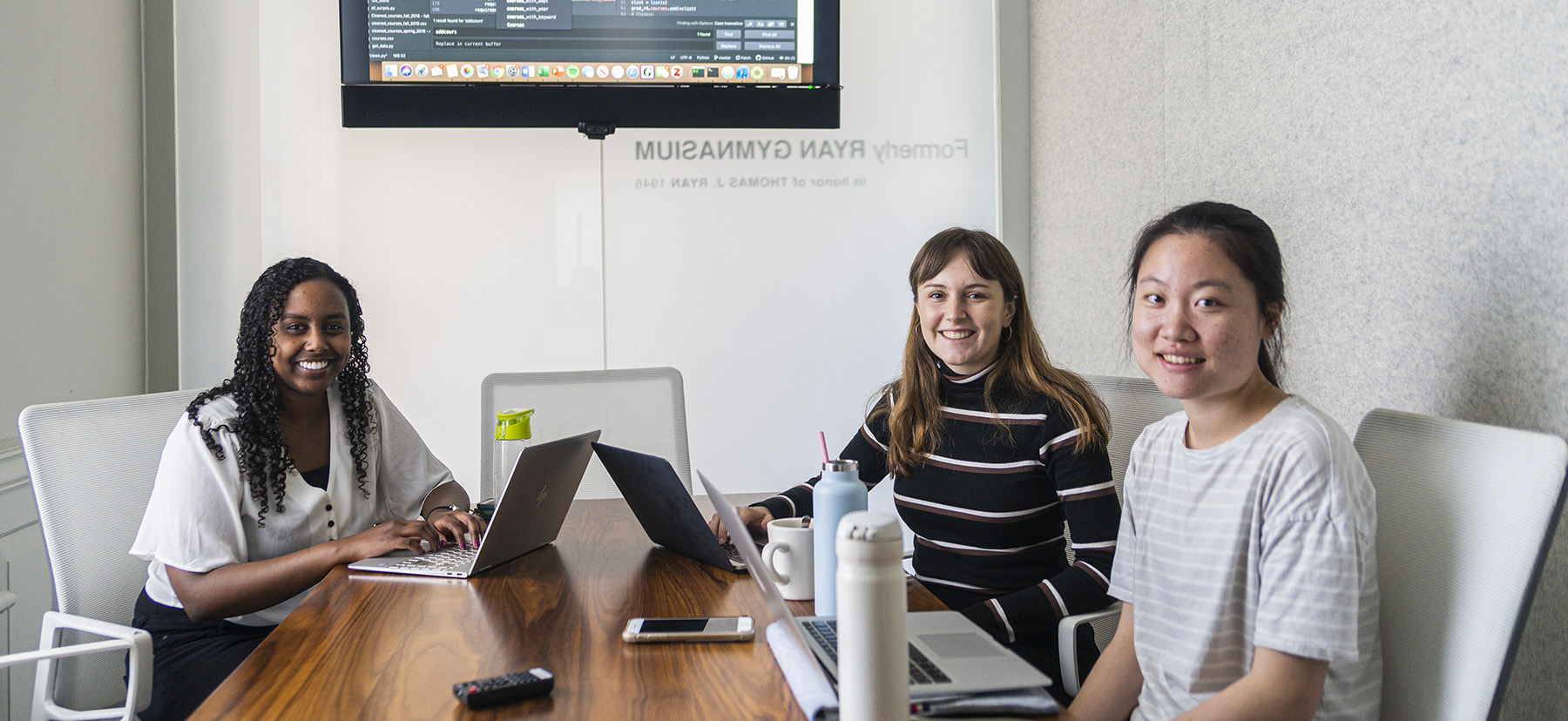 The three women who make up the Gradual incubator team work at laptops on their project